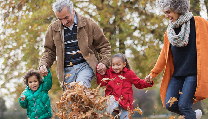 Elderly couple with young children playing in fallen leaves